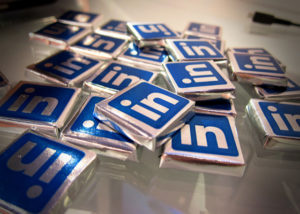Scattered chocolates, wrapped in silver foil labeled with the LinkedIn logo, on a table.